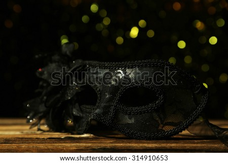 Female carnival mask with bokeh on brown wooden background - stock photo
