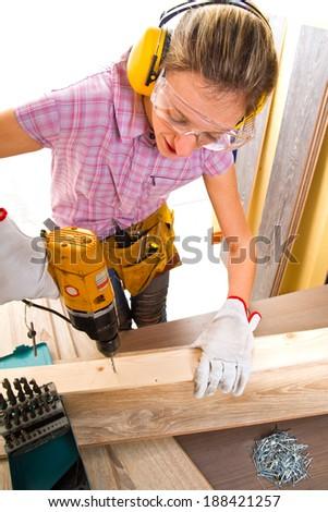 Female carpenter  at work using hand drilling machine - stock photo