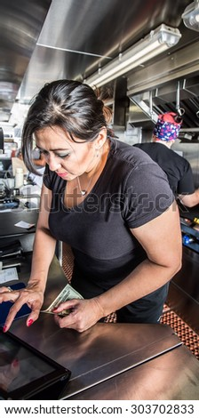 Female cashier with money on busy food truck - stock photo