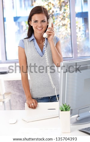 Female casual office worker talking on landline phone, smiling. - stock photo