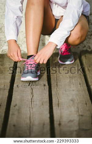Female caucasian athlete getting ready for running training. Woman tying sport footwear laces. Sport and healthy lifestyle concept. - stock photo