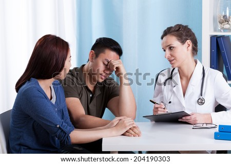 Female Caucasian doctor talking with her Asian patients - stock photo