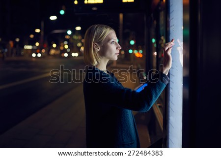 Female caucasian tourist touching information kiosk digital screen while standing outdoors at night city and holding smart phone in the hand, attractive young woman consults on modern big timetable - stock photo