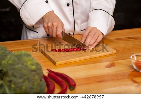 Female chef cutting pepper on wooden cutting board. Broccoli and pepper on the table.  - stock photo