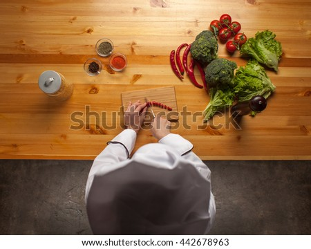 Female chef cutting pepper on wooden cutting board on wooden table with broccoli, salad leaves, tomatoes and pepper, top view - stock photo