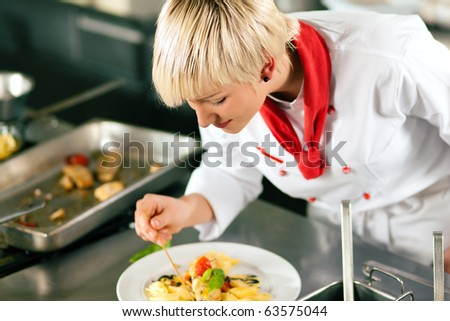 Female Chef in a restaurant or hotel kitchen cooking delicious food, both are finishing the dishes - stock photo
