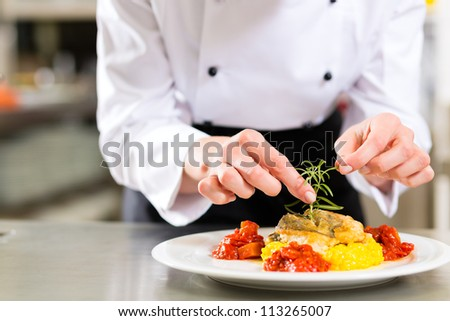 Female Chef in hotel or restaurant kitchen cooking, only hands, she is finishing a dish on plate - stock photo