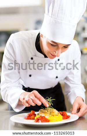 Female Chef in hotel or restaurant kitchen cooking, she is finishing a dish on plate - stock photo