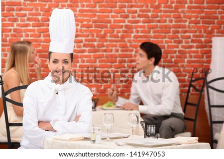 female chef posing in restaurant with couple dining in background - stock photo