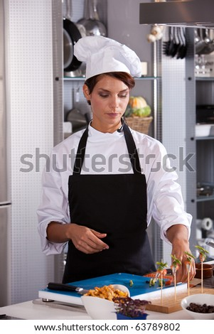 Female chef with headset giving a cooking demonstration to students - stock photo