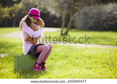 Female child alone sit on a suitcase - stock photo