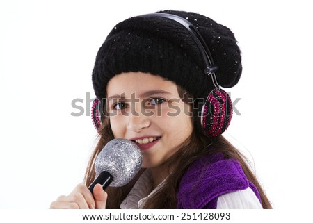 Female child singing with a mic and headphones - stock photo