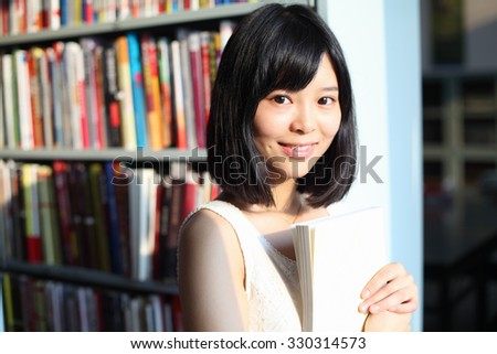 Female Chinese Student Holding Book in Library Smiling - stock photo