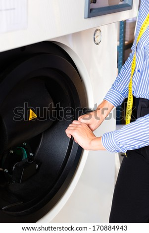 Female cleaner in laundry shop using cleaning machine for dry-cleaning - stock photo
