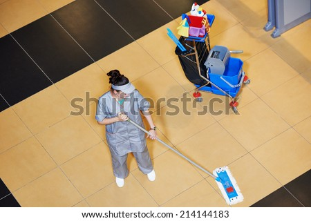 female cleaner with mop and uniform cleaning hall floor of public business building - stock photo