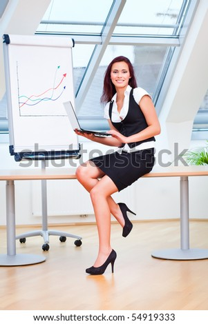 female clerk sitting on desk in office - stock photo