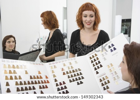 Female client and hairdresser selecting hair color from catalog in salon - stock photo