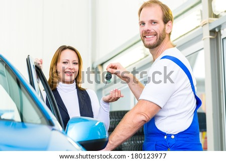 Female client and mechanic in auto workshop or MOT with car for service inspection - stock photo