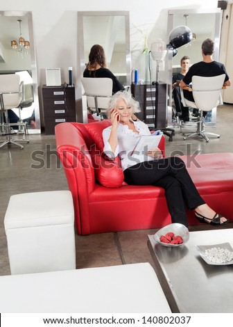Female client holding magazine while on call with customers in background at salon - stock photo