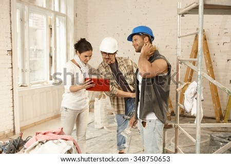 Female client showing plans on tablet computer to contractors, standing at renovation site. - stock photo
