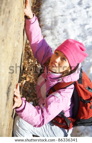 Female climber ascending the mountain - stock photo
