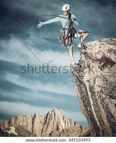 Female climber dangles from the edge of a challenging cliff. - stock photo