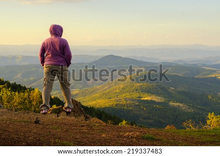 Female climber enjoying the view from the mountain top on sunny spring day. - stock photo