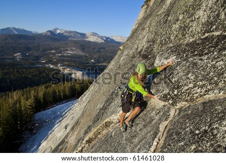 Female climber grips and scampers up a sheer rock wall in Yosemite's high Sierra Nevada mountains. - stock photo