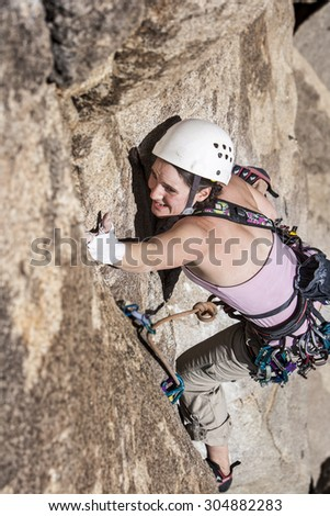 Female climber struggeling up a crack. - stock photo