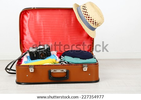 Female clothes and photo camera in old suitcase on light background - stock photo