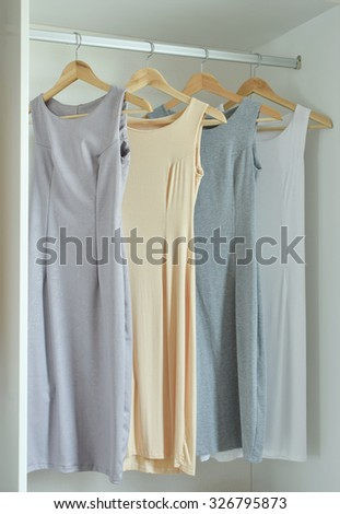Female clothes on hangers in wardrobe - stock photo