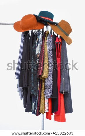 female clothes with hat hanging on clothes rack - stock photo