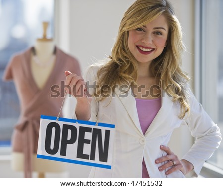 female clothing store worker opening up shop - stock photo