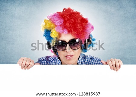 Female clown holding blank space on blue background - stock photo