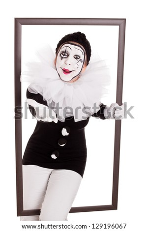 female clown in a frame is reaching hand to viewer - stock photo