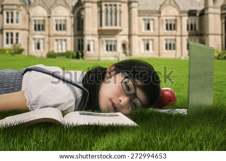Female college student sleeping on the grass at campus - stock photo