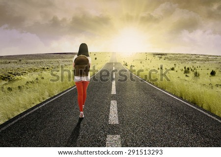 Female college student walk on the road to start her future - stock photo