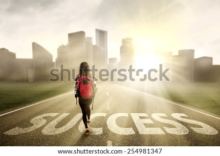 Female college student walk on the road to start her success - stock photo
