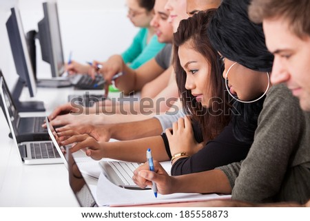 Female college students using laptop at desk in computer class - stock photo