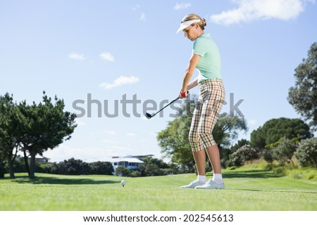 Female concentrating golfer teeing off on a sunny day at the golf course - stock photo