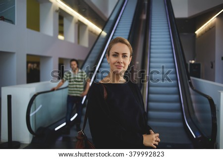 Female confident worker standing near escalator in airport before her business trip overseas, young intelligent woman employee posing below moving stairs in office center while waiting for partners - stock photo