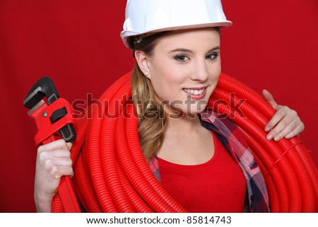 Female construction worker holding corrugated tubing and a pipe wrench - stock photo