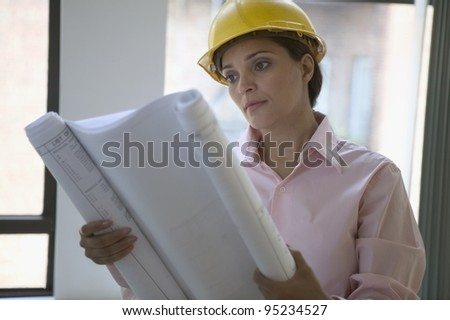Female construction worker reading blue prints - stock photo