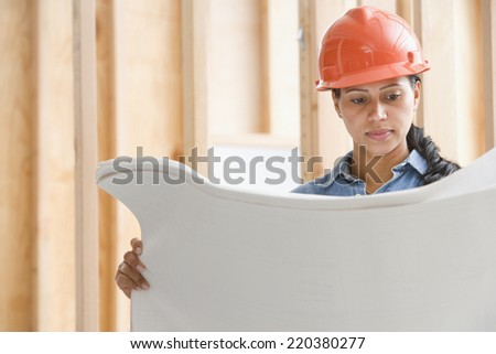 Female construction worker reading plans - stock photo