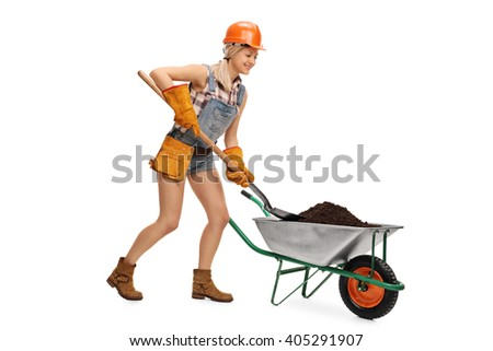 Female construction worker unloading a wheelbarrow full of dirt with a shovel isolated on white background - stock photo