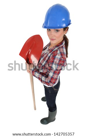 Female construction worker with a shovel - stock photo