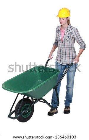 Female construction worker with a wheelbarrow - stock photo