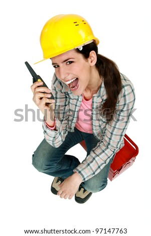 Female construction worker yelling into a walkie-talkie - stock photo