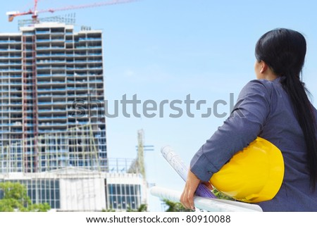 Female contractor or civil engineer looking at the building project on progress - stock photo