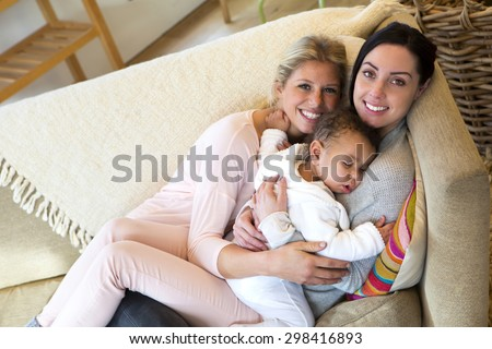 female couple cuddling on the sofa with their sleeping son - stock photo